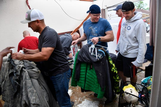 Fellow Airmen from Dyess Air Force Base collect the items of Francois Meyer after Saturday's storm blew the roof off his home and several others in the 4800 block of South Sixth Street in Abilene. Meyer is currently deployed, so his buddies came to rescue his things.
