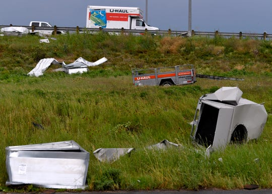 A U-Haul moving van passes another U-Haul trailer resting in the grass along the Winters Freeway.