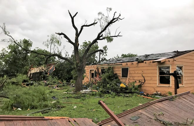The back yard of Tennille Woodard's home on Hawthorne Street shows the tornado storm damage in west Abilene on Saturday. The home next door received even more damage.