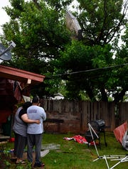 Amanda Crisp rests her head on the shoulder of her husband, Julius Crisp, as they look up at a mattress hanging in the tree over their home at 825 Alameda Road on Saturday. Destructive winds wreaked havoc across west Abilene in the early morning hours.