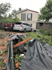 High winds knocked out a window and toppled a tree onto vehicles parked in a driveway on South San Jose Street in Abilene. May 18 2019