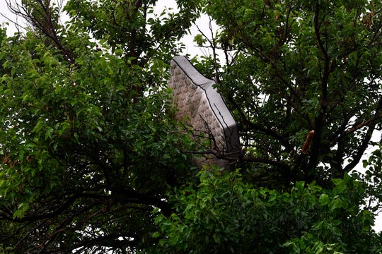 A mattress is suspended in a tree near Alameda Road after the May 18 tornado placed it there.