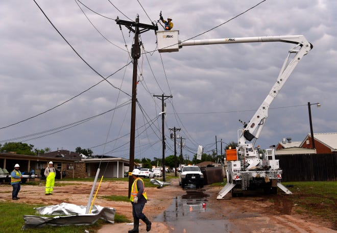 Utility workers repair lines behind Willow Springs Health and Rehabilitation Center after Saturday's storm.