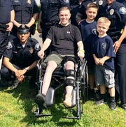 Camden County Police Officer Joseph Mair, center, has returned home after multiple surgeries after being struck by a  cab while on duty.