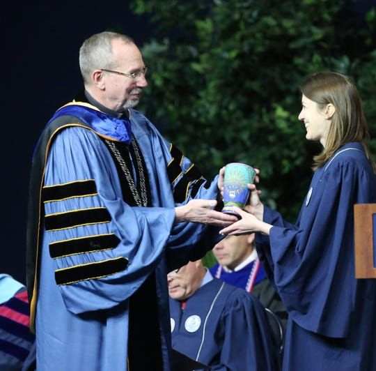 Xavier University President the Rev. Michael J. Graham gives the Magis Award to Margaret L. Weidener during the 181st  commencement ceremony  May 18.