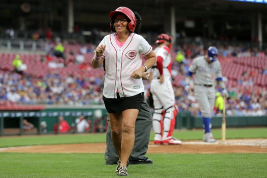 Cancer survivor Laura Fay, who served as the team's honorary bat girl, jogs back to the dugout after delivering balls to the home plate umpire in the first inning of an MLB baseball game against the Chicago Cubs, Thursday, May 16, 2019, at Great American Ball Park in Cincinnati.