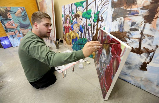 Christopher Billmyer works on an oil painting at Schmid Innovation Center in Dubuque on Thursday, May 9, 2019. Billmyer is a Dubuque native who lost both his legs in an explosion in Aghanistan. After graduating from University of Iowa this spring, he will return to Dubuque to open an art studio.