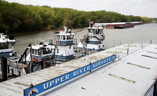 In this Tuesday, May 14, 2019 photo, empty barges, background right, are moored at the Upper River Services along with tug boats on the Mississippi River in St. Paul, Minn., as spring flooding interrupts shipments on the river. Historic Midwest flooding that began in March has left parts of the Mississippi River closed for business. (AP Photo/Jim Mone)