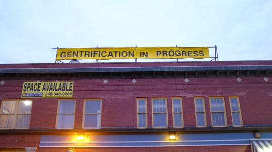 """Artist Ann Lewis and two assistants marked the Eastern Market businesses Supino Pizzeria, Russell Street Deli and Zeff's Coney Island with streams of yellow barricade tape and signs that read """"gentrification in progress"""" early morning May 18, 2019."""