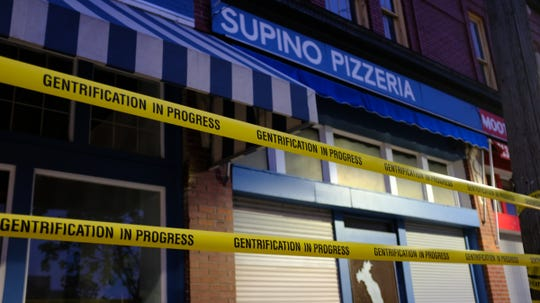 """Artist Ann Lewis and two assistants wrapped the entrances of Eastern Market businesses Supino Pizzeria, Russell Street Deli and Zeff's Coney Island with streams of yellow barricade tape that read """"gentrification in progress"""" early morning May 18, 2019."""