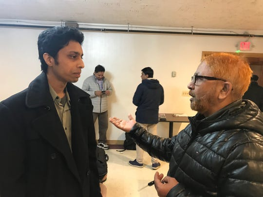 Pavan Vangipuram (left), the Detroit New Americans regional community coordinator, speaks with Md Layes Uddin, of Hamtramck, at a forum educating immigrants about becoming U.S. citizens on Jan. 13 , in a hall outside the Kabob House & Mouchack Sweets restaurant on Conant Ave. in Hamtramck.