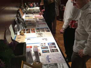 People look over memorabilia from Russ Gibb's life during a memorial event Friday for the late rock promoter, disc jockey and teacher at Ford Community & Performing Arts Center in Dearborn.