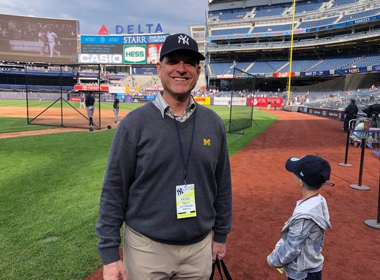 "Michigan football coach Jim Harbaugh and his son, Jack, stand on the field at Yankee Stadium before the New York Yankees' baseball game against the Tampa Bay Rays on Friday, May 17, 2019, in New York. He said he and his father had never been to Yankee Stadium before, and it's a ""bucket list"" trip for them."