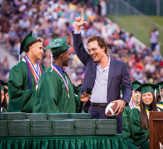 Longview Lobos Kamden Perry, left, and Jephaniah Lister present actor and 1988 Longview High School graduate Matthew McConaughey with an autographed football and his own state championship ring at the school's graduation ceremony in Longview, Texas, on Friday.