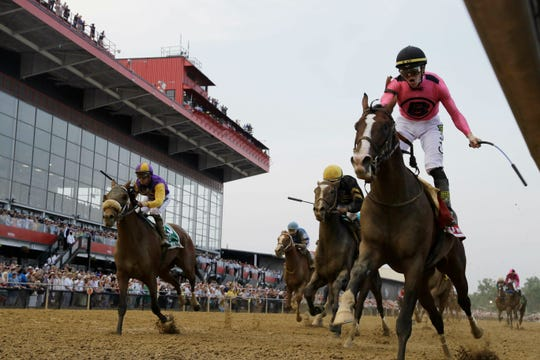 War of Will, ridden by Tyler Gaffalione, right, crosses the finish line first to win the Preakness Stakes horse race Saturday at Pimlico Race Course.