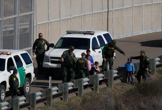 In this Dec. 9, 2018 file photo, a woman and children are ushered into cars by U.S. Border Patrol agents after crossing illegally over the border wall into San Diego, Calif., as seen from Tijuana, Mexico.