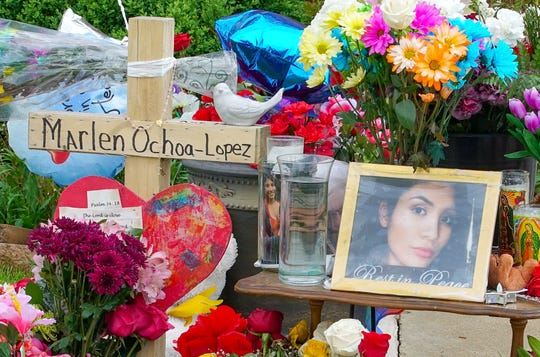 A memorial of flowers, balloons, a cross and photo of victim Marlen Ochoa-Lopez, are displayed on the lawn, Friday, May 17, 2019 in Chicago, outside the home where Ochoa-Lopez was murdered last month.
