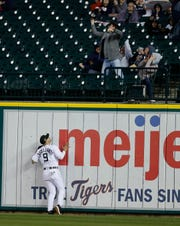 Tigers right fielder Nicholas Castellanos (9) watches as the two-run home run by Oakland Athletics' Mark Canha clears the wall during the fifth inning on Friday.