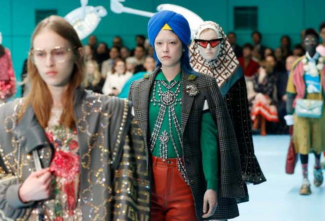 In this Feb. 21, 2018 file photo, models display items from Gucci's women's Fall/Winter 2018-2019 collection, presented during the Milan Fashion Week, in Milan, Italy.