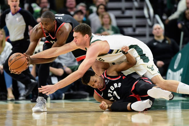Bucks center Brook Lopez battles Raptors guard Kyle Lowry (7) and center Serge Ibaka (9) for the ball during the second half of Game 2 on Friday.