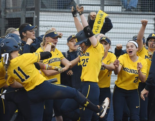 Michigan's Faith Canfield celebrates her  solo home run in the sixth inning of Friday's 8-0 win.