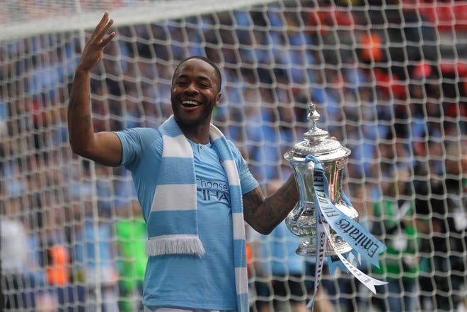 Manchester City's Raheem Sterling celebrates with the trophy after the English FA Cup Final soccer match between Manchester City and Watford Saturrday at Wembley Stadium in London.
