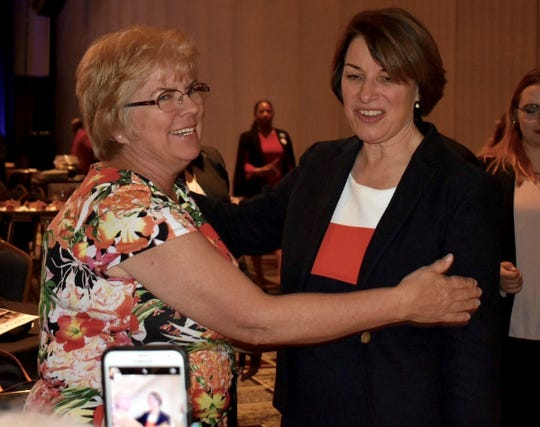 Carole Chi, left, chair of the Sterling Heights Democratic Club, greets U.S. Sen. Amy Klobuchar, D-Minnesota, after her keynote speech at the Michigan Democratic Party Women's Caucus 33rd Annual Legacy Luncheon on Saturday.