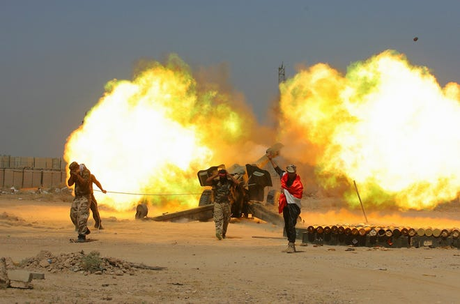 In this May 29, 2016 file photo, Iraqi security forces and allied Popular Mobilization forces fire artillery during fight against Islamic State militants in Fallujah, Iraq.