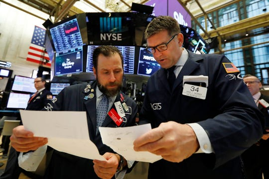 Specialists Michael Pistillo, left, and David Haubner confer on the floor of the New York Stock Exchange, Tuesday, May 14, 2019.
