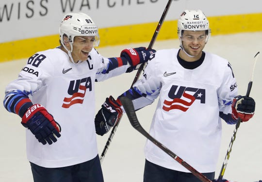 Alex Debrincat, right, celebrates with teammate Patrick Kane after scoring during the win over Denmark.