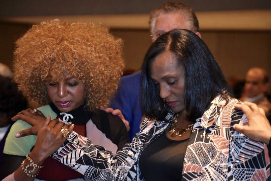 During the invocation by Lupe Ramos-Montigny, Kimberly Morgan, left, of West Bloomfield Township, and Theresa Clanton, Farmington Hills, joined hands and bowed their heads.