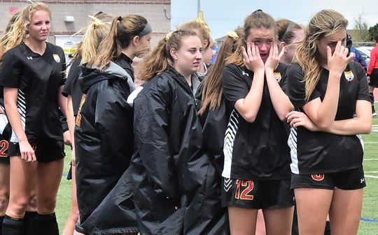 Players on Rocky Mountain High School's girls soccer team wipe tears from their eyes following a 3-2 loss to Arapahoe on Saturday in the Class 5A state semifinals at EchoPark Stadium in Parker.