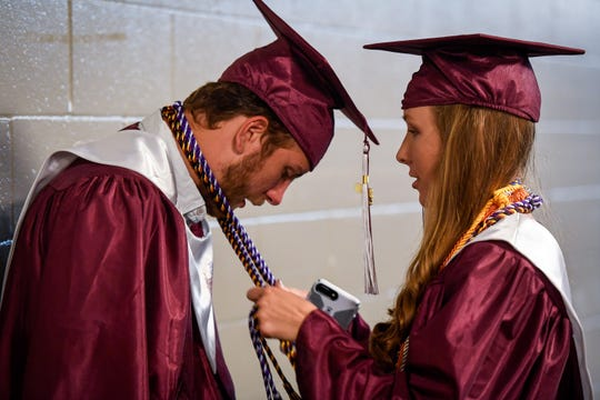 Maddie Griggs helps Ian Pitt with his tassels while the pair wait in the tunnel before the Henderson County High School 2019 Commencement Ceremony held at the Evansville Ford Center Friday evening.