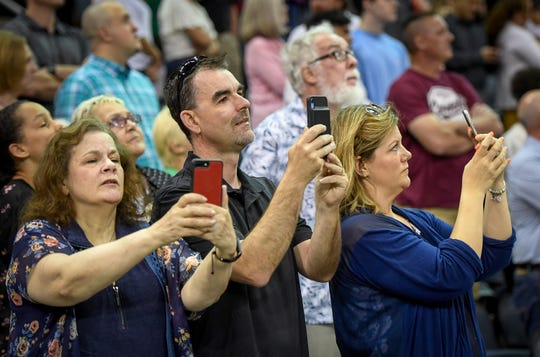 From left, Maureen Stephenson, Kevin Wesselman and Sarah Wesselman video and take photos of the Graduates Processional at the Henderson County High School 2019 Commencement Ceremony held at the Evansville Ford Center Friday evening.