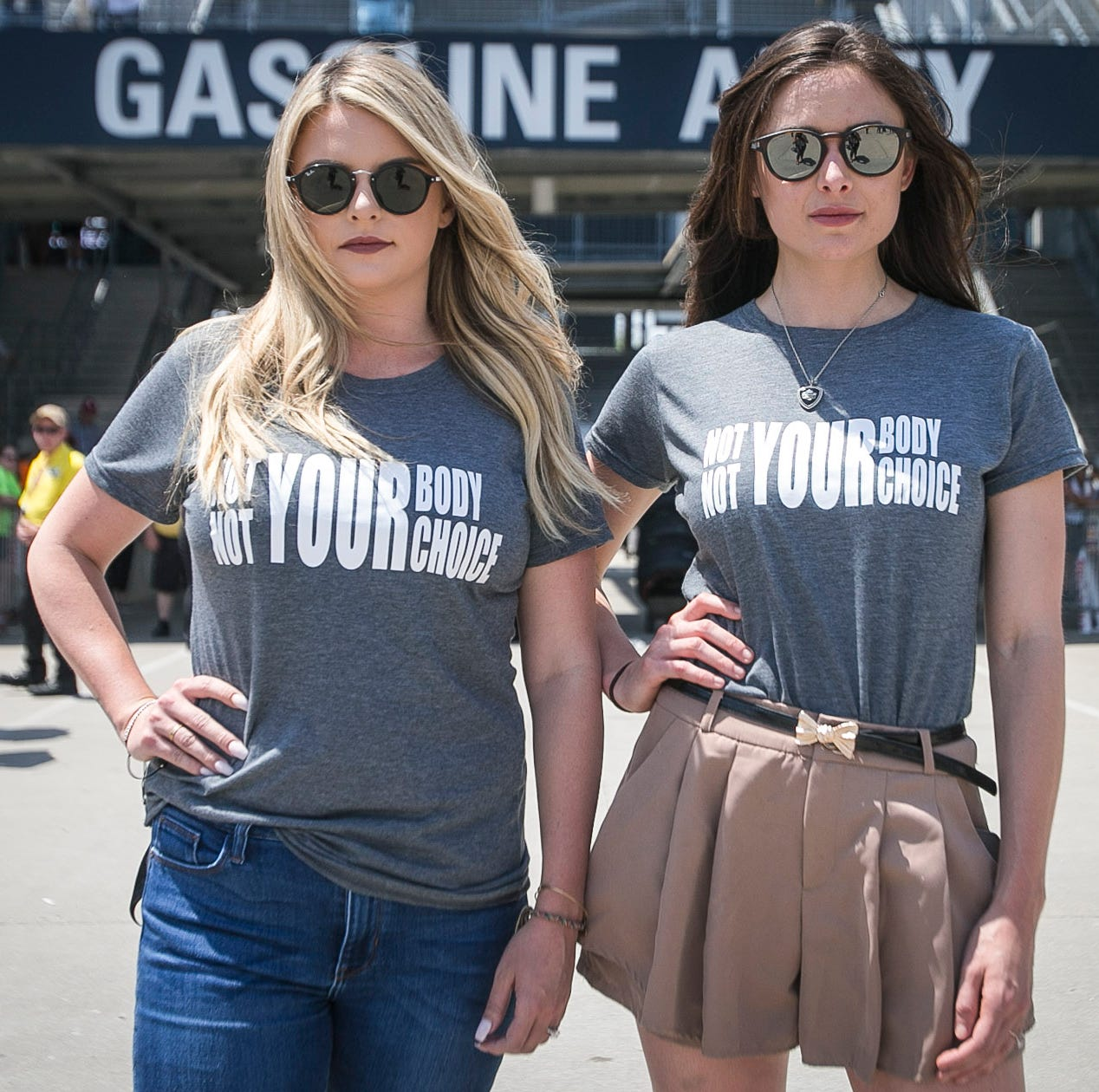 """Hailey McDermott, right, and Ashley Newgarden, left, fiancee and wife of Team Penske drivers Simon Pagenaud and Josef Newgarden, stand in Gasoline Alley at the Indianapolis Motor Speedway, Saturday, May 18, 2019, wearing """"Not YOUR Body, Not YOUR Choice"""" t-shirts in response of the recent passing of the restrictive Alabama abortion bill. ÒI understand it is uncomfortable for us to speak our mind especially about this right now, in the political climate we are in, that is not what we are trying to fight,"""" said McDermott, """"We are just trying to support the women that donÕt have that right now, but letÕs make the people who have done this to us uncomfortable."""""""