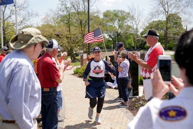 Cathy Powers carries an American flag as she runs towards the Gold Star Families memorial on Memorial Island, Saturday, May 18, 2019, at Columbian Park in Lafayette. Powers' late son, Senior Airman Bryce Powers, was killed while serving in the U.S. Air Force.