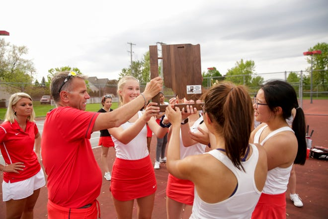 West Lafayette head coach Tim Wright hands the sectional trophy to his players after defeating McCutcheon in the IHSAA girls tennis team sectionals, Friday, May 17, 2019, at Cumberland Elementary School in West Lafayette.