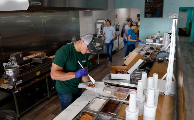 Dough-hio Donuts co-owner Trevor Griffith puts toppings on a doughnut Saturday morning, May 18, 2019, during the opening of doughnut shop on Memorial Drive in Lancaster. Griffith co-owns the shop with Jamie Moyer and Bill Davis.
