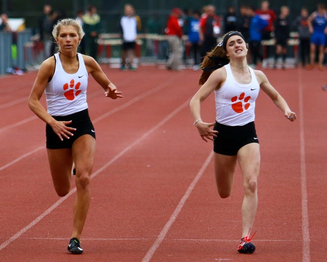 Morgan Waggoner (right) took first and Bryce Calka second for Brighton in the 400-meter run at the Division 1 track and field regional at Milford on Friday, May 17, 2019.