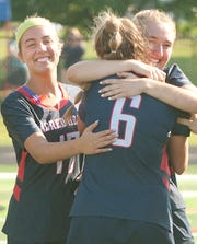 Sacred Heart midfielder Julia Jardina (back to camera) gets hugged by teammates after she was named the championship's most valuable player.