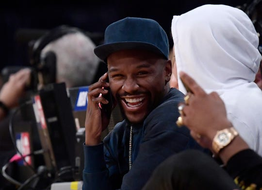 Boxer Floyd Mayweather Jr. talks on the phone during the second half of an NBA basketball game between the Los Angeles Lakers and the Minnesota Timberwolves on Thursday, Jan. 24, 2019, in Los Angeles. The Timberwolves won 120-105. (AP Photo/Mark J. Terrill)