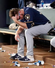 Brewers relief pitcher Corbin Burnes sits on the bench after being removed during the sixth inning after giving up three home runs.