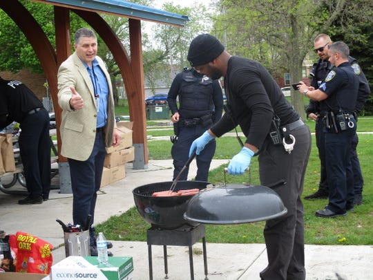 """Department of Neighborhood Services coordinator Mark Medrek talks to Milwaukee police as they grill hot dogs at the """"Where is the Love"""" event to raise awareness about domestic violence."""