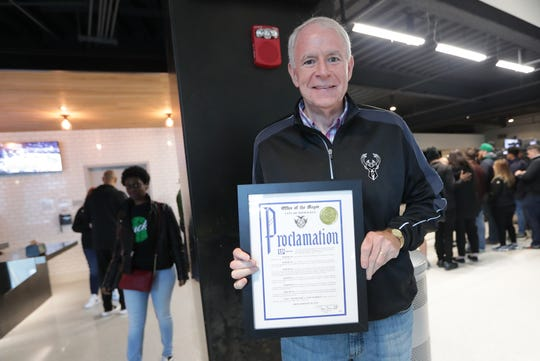 Mayor Tom Barrett holds the proclamation he gave to TNT broadcaster and Milwaukee 'homeboy' Ernie Johnson Jr. before Game 2 of the Eastern Conference finals.
