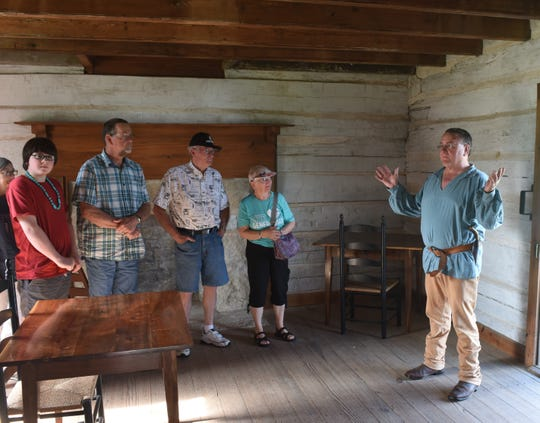 Jacob Wolf House Historical Site supervisor Marlon Mowdy (far right) explains the history of the Wolf House to a group of Pioneer Day visitors Saturday morning in Norfork.