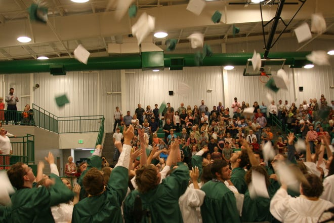 Members of Yellville-Summit's graduating class of 2019 toss their mortarboards into the air at the conclusion of last year's graduation ceremony. The school's 2020 seniors will have a belated graduation ceremony this Friday night at 9 p.m. at Panther Stadium.