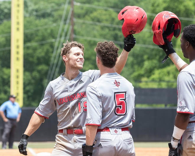 UL's Hunter Kasuls (19) celebrates his 3 run home-run with teammates Todd Lott (9) and Hayden Cantrelle (5) at home plate during the game against ULM at Warhawk Field in Monroe Saturday.