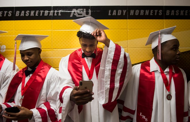 Darrel Brown, middle, adjusts his hat as he waits in the hallway during Robert E. Lee High School Graduation at the Dunn-Oliver Acadome in Montgomery, Ala., on Friday, May 17, 2019.
