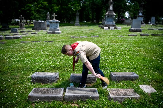 Ty Smith, 15, cleans off a gravestone Saturday, May 18, 2019, at Calvary Cemetery in Nashville.