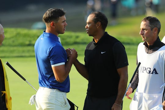 Brooks Koepka of the United States and Tiger Woods of the United States shake hands on the 18th green during the second round of the 2019 PGA Championship at the Bethpage Black course on May 17, 2019 in Farmingdale, New York.
